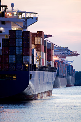 container cargo ships docked in port - three freighters sunset